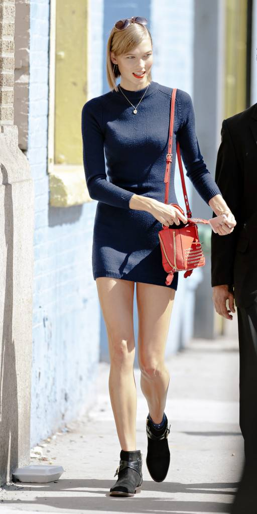 Karlie Kloss seen wearing blue sweater and red handbag while attending Mercedes Benz Fashion Week events in NYC. Image credit Coach and Splash news.